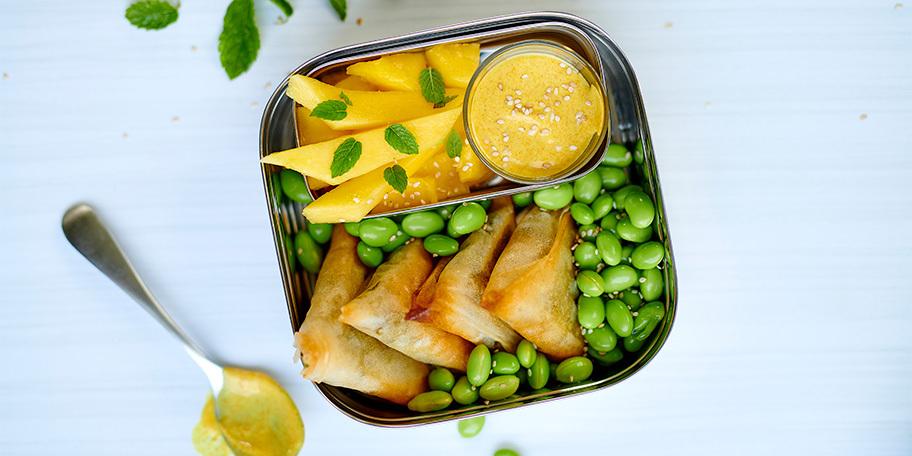 Lunchbox met samosa's, mango en edamameboontjes